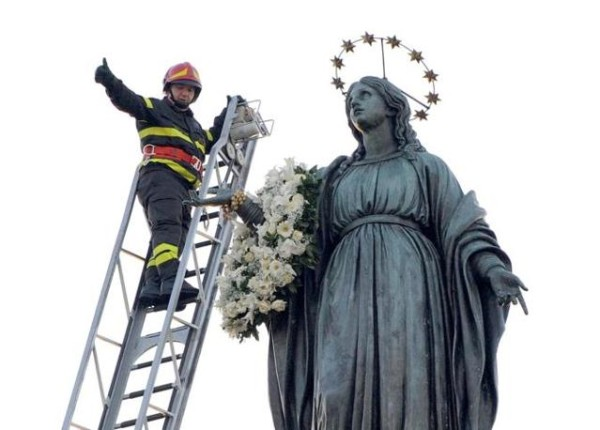 Il vigile del fuoco Antonio Vannacci depone la corona di fiori sulla statua della Madonna, come da tradizione, ogni anno, nel giorno dell'Immacolata, in piazza Mignanelli a Roma, 8 dicembre 2011. ANSA/MARIO DE RENZIS